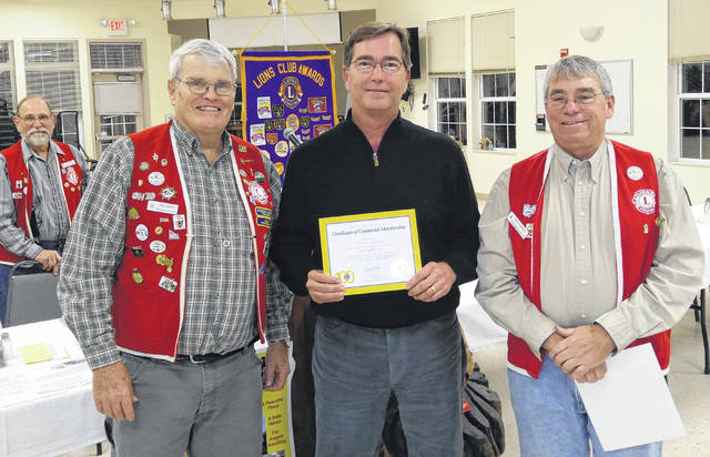 At the new member ceremony are, from left: Lion Nial Henry, Induction Officer; new member Matt Williams; and Lion Rick Kneisel, Sponsor Lion. Club President John Beireis is in the background.