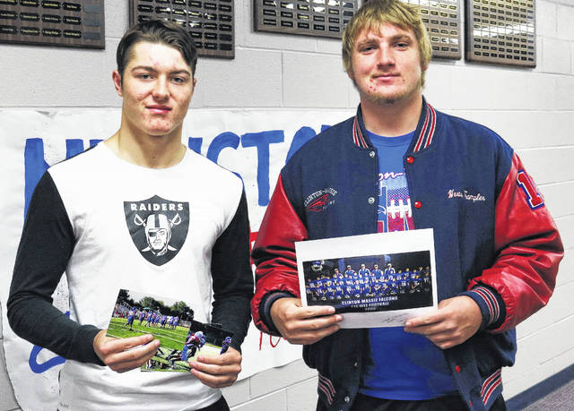 CM senior football players Christian Poynter and Weston Trampler looked over some old team photographs. Several CM seniors have been playing together on the same team for 10 years.