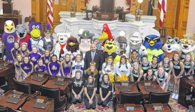 House Speaker Cliff Rosenberger is surrounded by college mascots — including Quakerman, just behind the speaker's right shoulder — and cheer squads in the statehouse chamber.