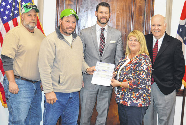 The Clinton County Fair Board presented two checks to county commissioners Monday: an $8,166 check to pay off an arrearage to the county early; and a $300,000 check to reimburse funds that commissioners up fronted on grant dollars the Fair Board had been awarded by government agencies but which the Fair Board did not yet have in hand. From left are Fair Board members Tom Thatcher and Scot Gerber, and Clinton County Commissioners Kerry R. Steed, Brenda K. Woods and Patrick Haley.