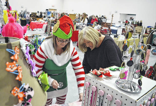 An elf — Christy Meade of Leesburg —assists Evelyn Pentzer at the annual Christmas Around Sabina Town event. Many of the crafts people had booths Friday and Saturday in the fellowship hall at the new Sabina Church of Christ as pictured. More than a dozen homes in the area, as well as a number of businesses, eateries and The C.O.V.E. were destination points, too, as people shopped and visited with one another. By the way, Pentzer is the Fayette County clerk of courts.
