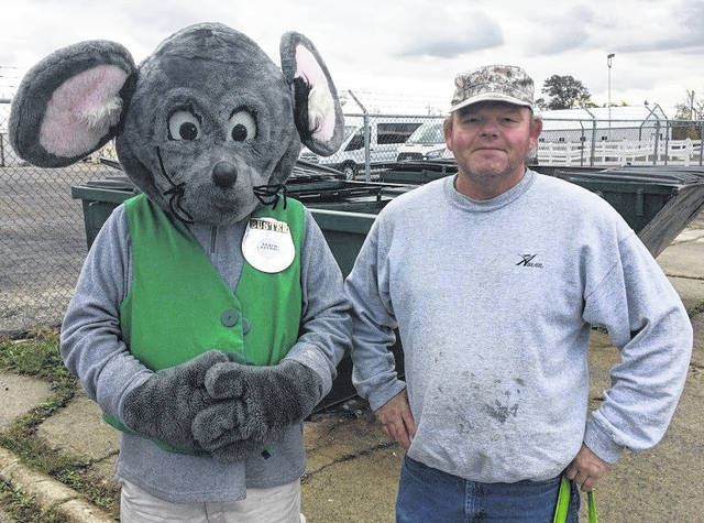 "Dean Johnson is today's ""Get Caught Recycling"" culprit of the week — Buster the Mouse, from the Clinton County Solid Waste District, caught Dean ""green-handed"" putting the proper recyclables into the community drop-off recycling containers located in Wilmington. This year's Get Caught Recycling theme is Rest & Relaxation. For his efforts in practicing the 3 R's, Dean received several recycled content prizes, such as a hammock, shopping bag, and reusable litter bag, just to name a few. Don't miss out on this chance to win great prizes by simply recycling household items such as bottles, jars and newspapers. For a list of the local recycling drop-off locations and acceptable materials, visit www.co.clinton.oh.us/recycling. There is only one week left in the campaign, so be on the lookout … you could be the next person caught green-handed!"