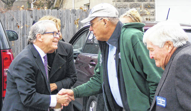 Running for the office of Ohio governor, Mike DeWine, left foreground, greets Wilmington Mayor John Stanforth outside the Kava House on Wednesday. Directly behind DeWine in the photo is his wife Fran, mostly hidden.
