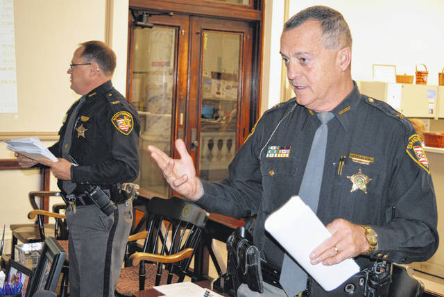 With the budget meeting between Clinton County commissioners and sheriff's office leaders concluded, Sheriff Ralph D. Fizer Jr., in the right foreground, and Chief Deputy Brian Prickett, left background, chat with individual commissioners.