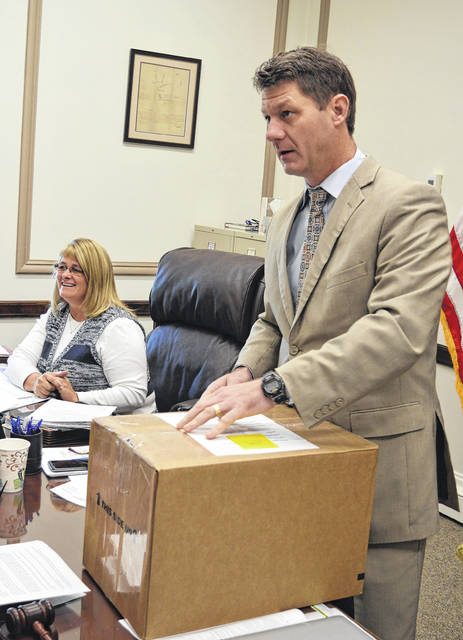 Clinton County Commissioners President Kerry R. Steed, foreground, prepares to open a box containing several copies of the Council on Aging of Southwestern Ohio's proposal to remain the administrator of funds from the Clinton County senior services levy. Clinton County Commissioner Brenda K. Woods is in the background.