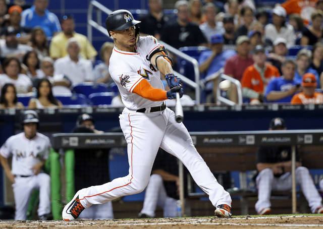 FILE - In this June 23, 2017, file photo, Miami Marlins' Giancarlo Stanton hits a home run in the third inning of a baseball game against the Chicago Cubs in Miami.  A person familiar with the negotiations says the New York Yankees and Miami Marlins are working on a trade that would send slugger Giancarlo Stanton to New York and infielder Starlin Castro to Miami.  The person spoke to The Associated Press on condition of anonymity Saturday, Dec. 9, 2017, because no agreement has been completed. (AP Photo/Wilfredo Lee, File)