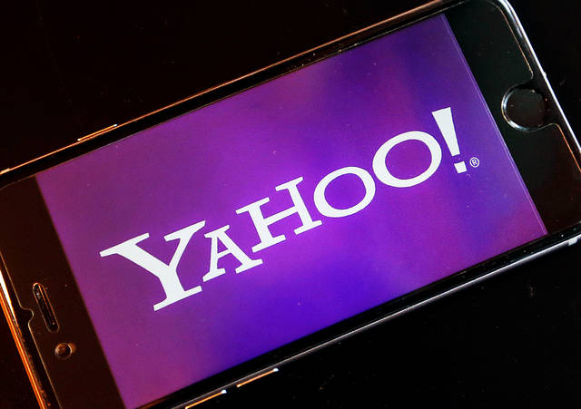 FILE - In this Dec. 15, 2016, file photo, the Yahoo logo appears on a smartphone in Frankfurt, Germany. Watching NFL games free on your phone used to be mainly limited to Verizon customers. Soon anyone will be able to download Yahoo's app and watch football games on the go. Verizon's new deal with the NFL goes into effect in January 2018 and will last for several years. Verizon bought Yahoo in June 2017 and is trying to build a digital ad business to rival Facebook and Google. (AP Photo/Michael Probst, File)