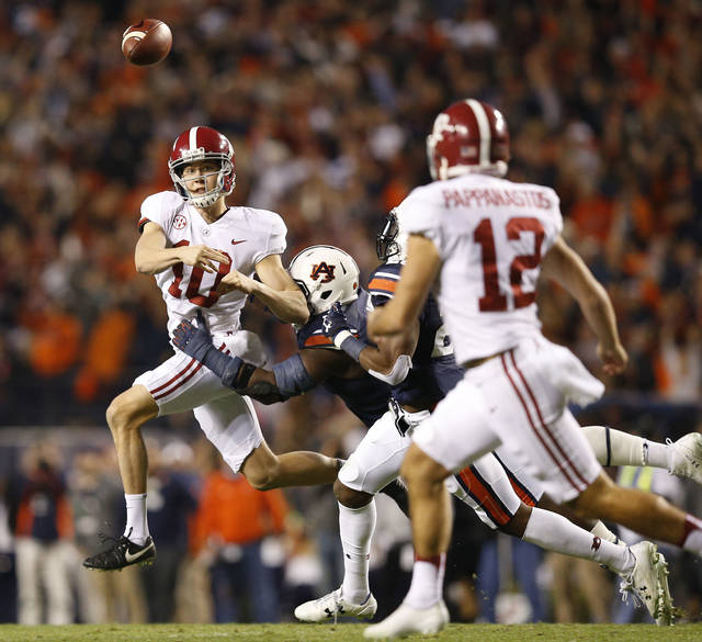 In this Nov. 25, 2017, photo, Alabama punter JK Scott throws the ball against Auburn defensive lineman Marlon Davidson during the second half of the Iron Bowl NCAA college football game in Auburn, Ala. We have some bad news. Well, it's not really news because it happened months ago, but since there is a good chance you were not paying attention when the Poinsettia Bowl passed away back in January you might be saddened to find out there are less FBS bowl games this season than last. (AP Photo/Brynn Anderson)