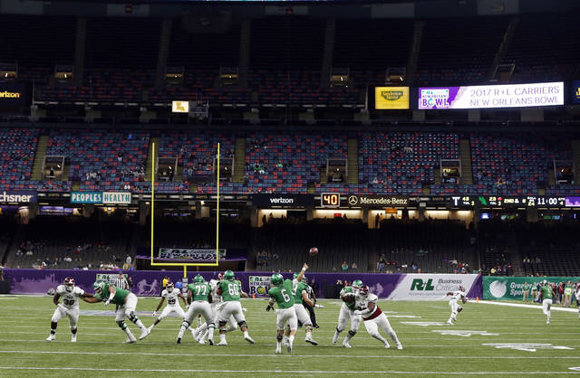 Empty seats are seen in the second half of the New Orleans Bowl NCAA college football game between Troy and North Texas in New Orleans, Saturday, Dec. 16, 2017. Group of Five teams will mostly play in third-tier bowl games in front of sparse crowds, earning payouts that mostly cover travel expenses. The Power Five teams get the glamor bowls with the multimillion-dollar payouts. (AP Photo/Gerald Herbert, File)