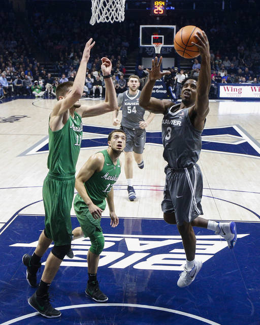 Xavier's Quentin Goodin (3) shoots against Marshall's Ajdin Penava (11) and Jarrod West (13) in the first half of an NCAA college basketball game, Tuesday, Dec. 19, 2017, in Cincinnati. (AP Photo/John Minchillo)