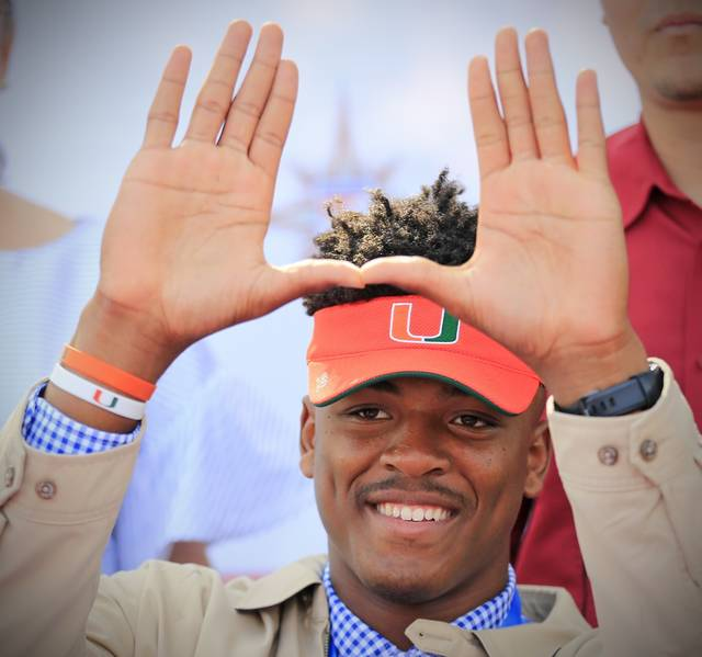 """Gregory Rousseau, a Champagnat Catholic High School football player, makes a """"U"""" gesture announcing his intentions to attend the University of Miami during the NCAA college football early signing period, Wednesday, Dec. 20, 2017, in Sunrise, Fla. (Al Diaz/Miami Herald via AP)"""