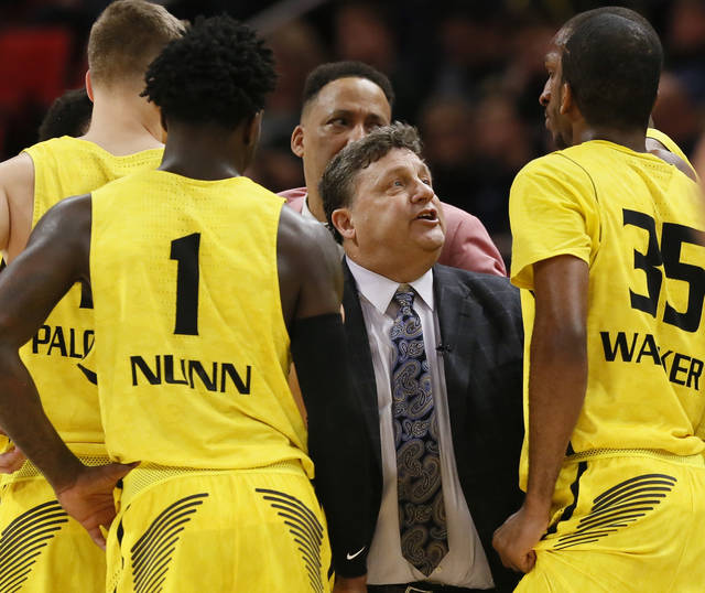 FILE - In this Dec. 16, 2017, file photo, Oakland coach Greg Kampe talks to guards Martez Walker (35) and Kendrick Nunn (1) during a timeout in the second half of an NCAA college basketball game against Michigan State on Saturday, Dec. 16, 2017, in Detroit. Oakland is 0-16 against Michigan State after an 86-73 loss to the second-ranked Spartans last weekend, and after the game, Kampe was blunt in saying how upset he was that his team couldn't pull off the upset. Oakland has built a solid mid-major program that can compete with big-name schools, but without a signature accomplishment--like an NCAA Tournament run or a win over a team like Michigan State--it's hard to get noticed. (AP Photo/Duane Burleson, File)