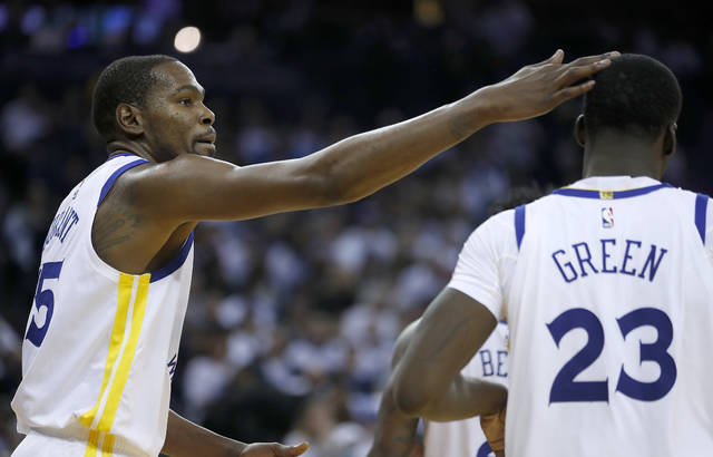 Golden State Warriors forward Kevin Durant (35) taps forward Draymond Green (23) on the head after scoring against the Cleveland Cavaliers during the second half of an NBA basketball game in Oakland, Calif., Monday, Dec. 25, 2017. The Warriors won 99-92. (AP Photo/Tony Avelar)