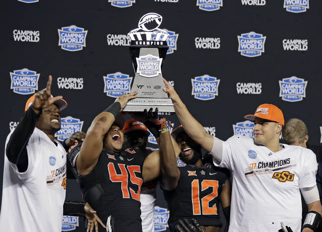 Oklahoma State players, from left, Tre Flowers, Chad Whitener (45), Kirk Tucker (12) and quarterback Mason Rudolph hold up the trophy after Oklahoma State defeated Virginia Tech 30-21 in the Camping World Bowl NCAA college football game Thursday, Dec. 28, 2017, in Orlando, Fla. (AP Photo/John Raoux)