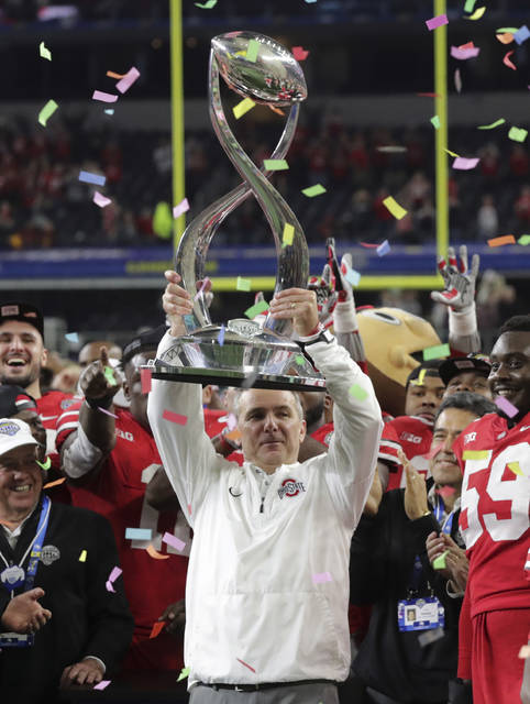 Ohio State coach Urban Meyer lifts the trophy after the Cotton Bowl NCAA college football game against Southern California in Arlington, Texas, Friday, Dec. 29, 2017. Ohio State won 24-7. (AP Photo/LM Otero)