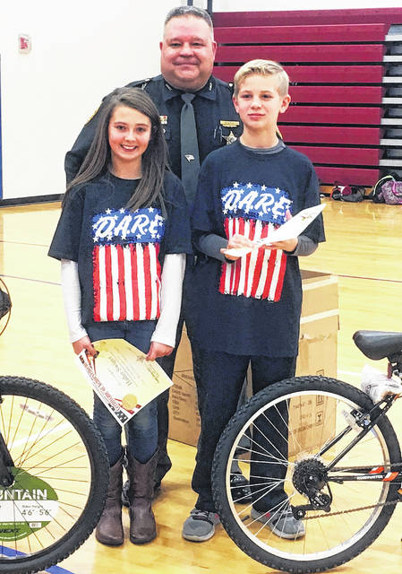 D.A.R.E. instructor and School Resource Officer Deputy Danny Wood is shown with first-place essay contest winners Hailey Swiger and Brendan Musser. Swiger and Musser each received a new bicycle for their winning essays.