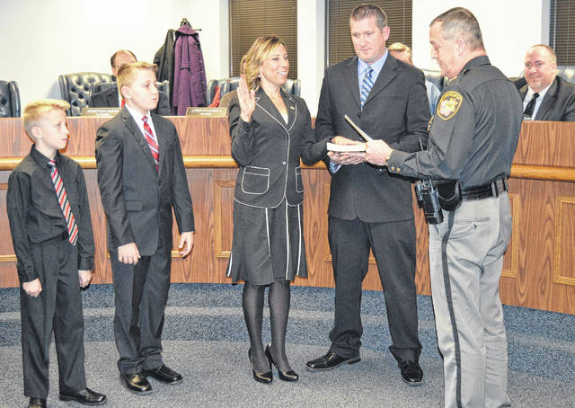 New Wilmington City Council Member Kristi Fickert is sworn in to office for her term beginning Jan. 1 by her uncle, Clinton County Sheriff Ralph D. Fizer Jr., during Thursday night's council meeting before a packed house as her husband and sons look on.