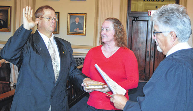 """Robin King, left, is sworn in as a member of Port William Village Council on Wednesday, as his fiancé Debbie Lynch stands by and Clinton County Common Pleas Judge John W. """"Tim"""" Rudduck makes it official."""