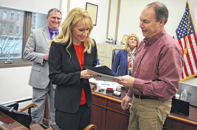 From left in the foreground, Blanchester Pool and Recreation Center project committee Chairperson Erin Whitaker provides contact information to State Sen. Bob Peterson. Looking on in the background are project committee Treasurer Doug Naylor and Clinton County Commissioner Brenda Woods.