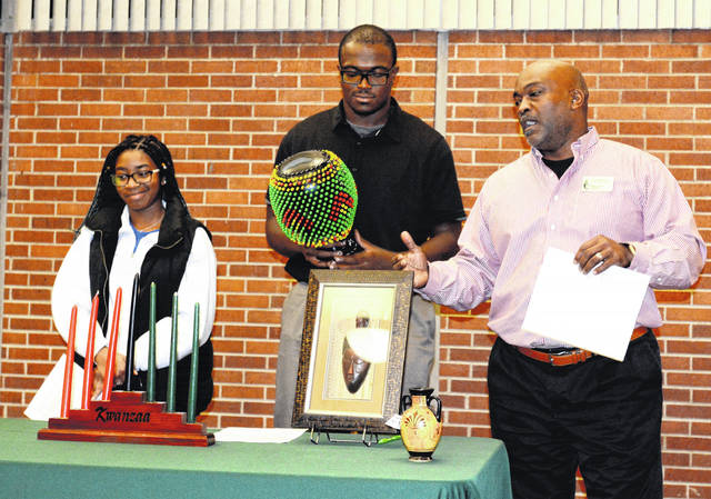 Chip Murdock (right), director of diversity and inclusion, explains some of Kwanzaa's finer points along with Black Student Initiative members Kelly Angevine and Sterling Clark, the latter of whom is holding a ceremonial skekere, a rhythm percussion instrument from Africa.