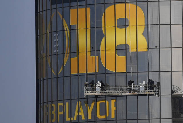 Workers place signage on a hotel announcing the NCAA national championship football game, Wednesday, Jan. 3, 2018, in Atlanta. Alabama and Georgia won their College Football Playoff semifinals on Monday and will meet in the national championship next week in Atlanta. (AP Photo/Mike Stewart)