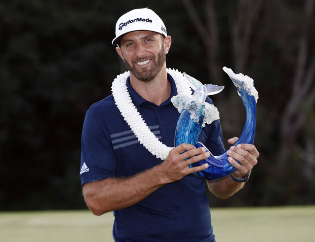 Dustin Johnson poses with the champions trophy for photographers after the final round of the Tournament of Champions golf event, Sunday, Jan. 7, 2018, at Kapalua Plantation Course in Kapalua, Hawaii. Johnson shot a 24 under par for the victory. (AP Photo/Matt York)