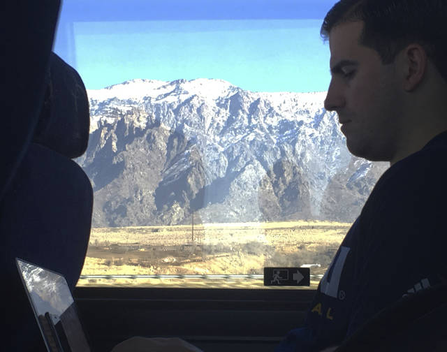 In this Jan. 5, 2018, photo, Northern Arizona assistant basketball coach Jason Sanchez goes over game film from the night before on a bus ride to Pocatello, Idaho. The Lumberjacks lost to Weber State by 40, then had to leave the next day on a two-hour bus ride for a game against Idaho State before driving back through Ogden to Salt Lake City. (AP Photo/John Marshall)
