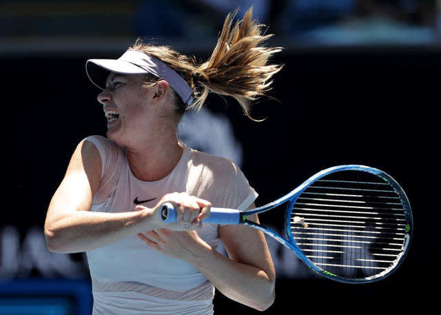 Russia's Maria Sharapova follows through on a shot to Germany's Tatjana Maria during their first round match at the Australian Open tennis championships in Melbourne, Australia, Tuesday, Jan. 16, 2018. (AP Photo/Vincent Thian)