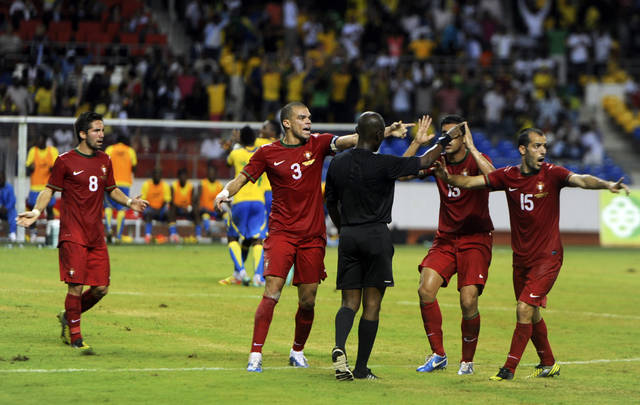 "FILE - In this Wednesday, Nov. 14, 2012 file photo, Portugal players including Pepe, center left, argue with referee Joseph Lamptey during their international friendly soccer match against Gabon in Libreville, Gabon. A FIFA investigation linked a referee accused of match-fixing a World Cup qualifier in 2016 to ""numerous publicly documented scandals"" in the previous six years. FIFA investigators said Joseph Lamptey of Ghana had ""a history of being suspended for poor performances"" before being banned for life and typically awarded more penalties than other African referees of his grade. Portugal's 2-2 draw in Gabon in a 2012 friendly, which included three penalties scored, was among six games identified as suspicious that Lamptey handled before the game that ended his career. (AP Photo/Joel Bouopda Tatou, file)"