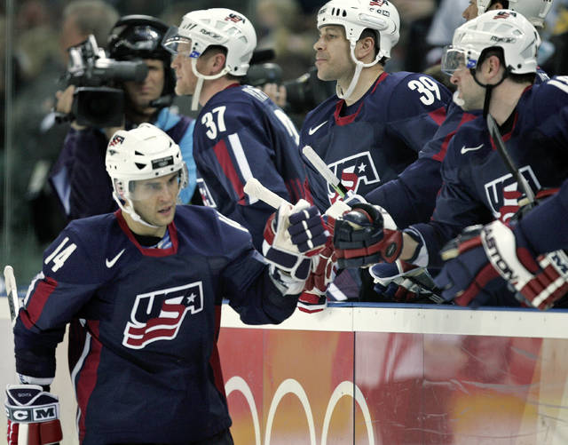 FILE - In this Feb. 15, 2006, file photo, United States' Brian Gionta (14) is congratulated by teammates after scoring against Latvia during a 2006 Winter Olympics men's ice hockey match, in Turin, Italy. When Gionta last played in the Olympics in 2006, his final NHL game before the break allowed him just three days to fly to Italy and get acclimated before suiting up for the United States. It won't be so much of a whirlwind this time around for the semi-retired U.S. captain and his Olympic teammates, who will get four whole practice days before opening the tournament against Slovenia on Feb. 14. (AP Photo/Gene J. Puskar, File)