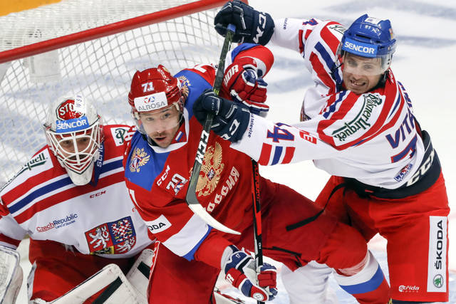 FILE - In this Dec. 16, 2016, file photo, Russia's Ilya Kovalchuk, center, tries to score as Czech Republic's Ondrej Vitasek, right, and Dominik Furch make a challenge during the Ice Hockey Channel One Cup match in Moscow. Russia is considered the favorite for gold in the upcoming Olympics because it has former NHL players Kovalchuk, Pavel Datsyuk and Andrei Markov. (AP Photo/Pavel Golovkin, File)
