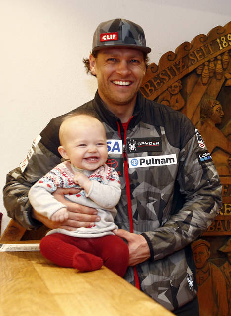 United States' Steven Nyman holds his daughter Nell poses for a photograph in Kitzbuehel, Austria, in this Jan. 19, 2018 photo. Diaper bags and baby backpacks are in just as much demand as skis, boots and poles on the U.S. Alpine team this Olympic season. (AP Photo/Giovanni Auletta)