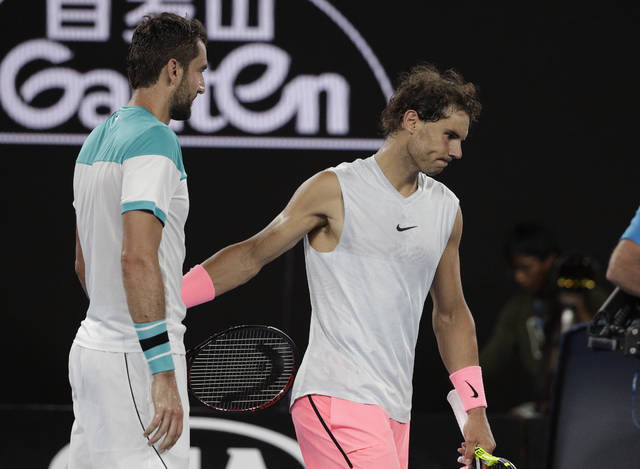 Spain's Rafael Nadal, right, walks from Croatia's Marin Cilic after he withdrew injured from their quarterfinal at the Australian Open tennis championships in Melbourne, Australia, Tuesday, Jan. 23, 2018. (AP Photo/Dita Alangkara)