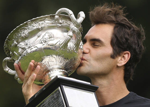 Switzerland's Roger Federer kisses the Norman Brookes Challenge Cup after winning the men's singles final at the Australian Open against Croatia's Marin Cilic in Melbourne, Australia Monday, Jan. 29, 2018. (AP Photo/Dita Alangkara)