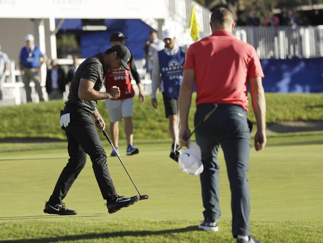 Jason Day, of Australia, left, reacts after making his putt on the 18th hole of the South Course at Torrey Pines Golf Course to win the Farmers Insurance Open golf tournament during a playoff hole, Monday, Jan. 29, 2018, in San Diego. Alex Noren, of Sweden, looks on at right. (AP Photo/Gregory Bull)