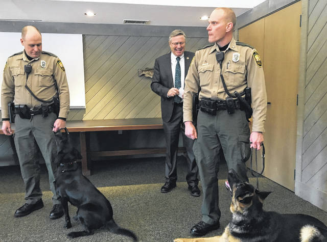 Ohio Department of Natural Resources (ODNR) Director James Zehringer looks on as some of the K-9s from the ODNR Division of Wildlife's new wildlife K-9 program are introduced to the public. Pictured are (left to right): Matt Leibengood, wildlife officer for Sandusky County, with May, and Jeremy Carter, wildlife officer for Holmes County, with Finn.