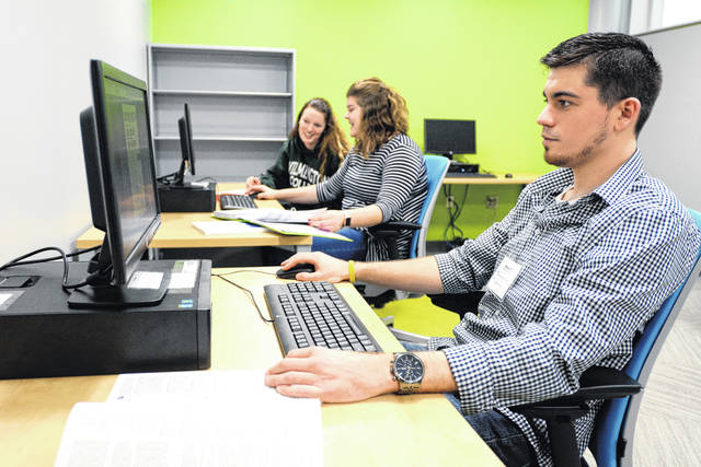 Wesley Pierson works on a tax return at WC's VITA site, along with Tara Karnes and Aubrey Richardson, during the 2017 tax season.