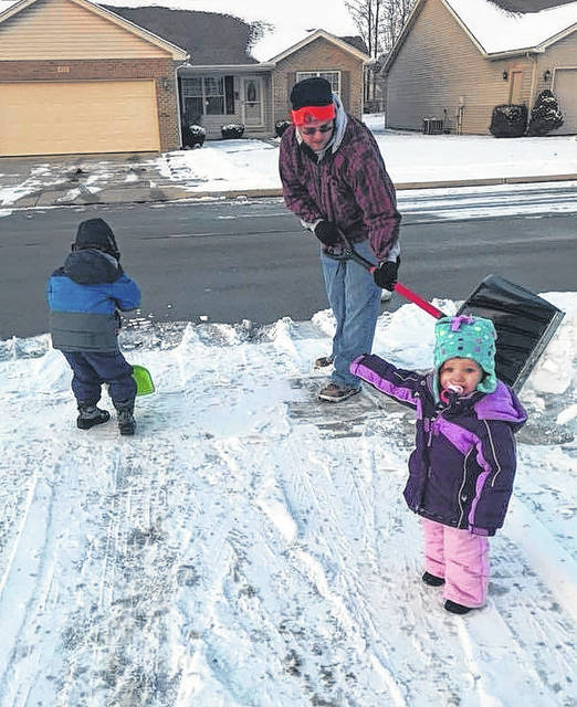 Adam Holbrook gets some shoveling help from son Henry, 4, and some supervision from daughter Violet, 2, to dig out of Monday's ice and slush in Wilmington. Southwest Ohio quickly warmed up after the icy beginning to the week, but cold temps are again on the horizon for this weekend begging around Friday night.