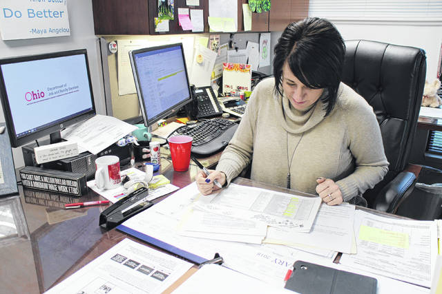 Highland County Job and Family Services Director Katie Adams reviews a spreadsheet in her office on Monday detailing the number of children removed from homes in previous years.