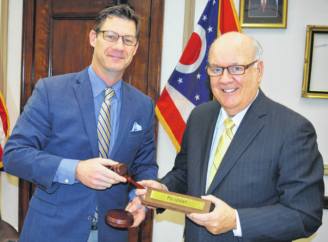 From left, Clinton County Commissioner Kerry R. Steed hands off the president's gavel Monday to Clinton County Commissioner Patrick Haley, who will be the commissioners' president in 2018.