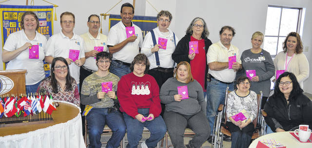 Holding up Valentine gift packets they assembled for cancer center patients, members of the Aktion Club take time out Thursday for a group photograph, joined by two women on the staff of the Foster J. Boyd, MD, Regional Cancer Center. From left in the back row are April Williams, David Burton, Raymond Bickel, Jon Arrington, Frank Powell, Barb Florea, Todd Bickel, Cancer Center social worker Michelle Roth and Cancer Center certified tumor registrar Diane Fawley; and from left in the front row are Aktion Club coordinator Sarah Edwards, Jerrod Rangel, Rachael Hinman, Jenny Rocheleau, Amy Grooms and Sarah Morgan, a staffer with Person Centered Services (PCS) which partners with Orion, Inc.