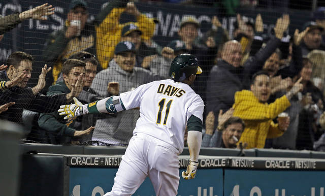 FILE - In this April 4, 2017, file photo, Oakland Athletics' Rajai Davis celebrates with fans as he scores on a throwing error after hitting a two-run triple off Los Angeles Angels' Bud Norris during the seventh inning of a baseball game in Oakland, Calif. The Athletics will expand protective netting between the stands and the playing field to the far ends of both dugouts ahead of the 2018 season.(AP Photo/Ben Margot, File)
