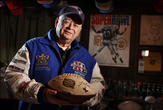 In this Thursday, Jan. 25, 2018 photo Donald Crisman poses with memorabilia from the 51 Super Bowls he has attended so far, at his home in Kennebunk, Maine. Crisman been to every Super Bowl and plans to attend this year's game between New England and Philadelphia in Minneapolis. (AP Photo/Robert F. Bukaty)