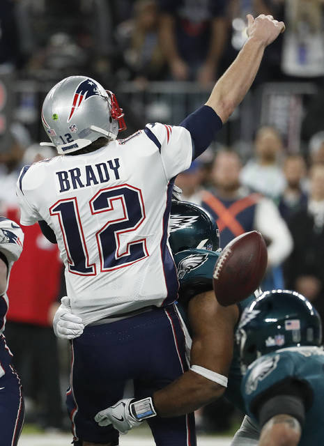 Philadelphia Eagles' Brandon Graham, center, strips the ball from New England Patriots quarterback Tom Brady during the second half of the NFL Super Bowl 52 football game Sunday, Feb. 4, 2018, in Minneapolis. The Eagles recovered the fumble. (AP Photo/Matt York)