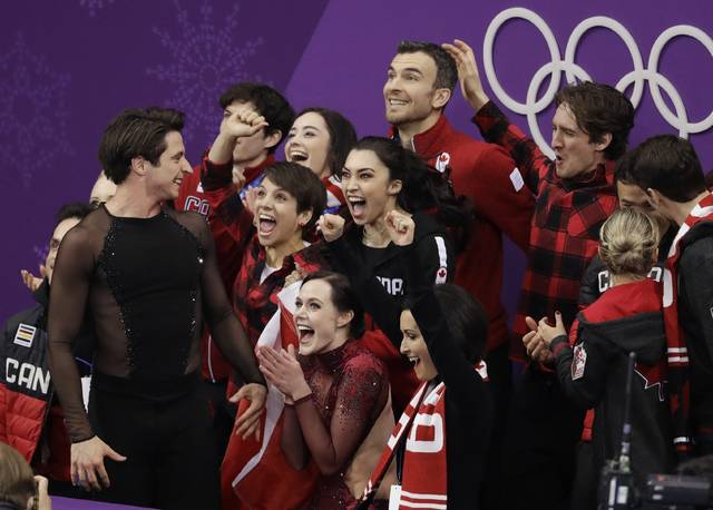 Scott Moir and Tessa Virtue of Canada celebrate with teammates after their score was posted in the ice dance free dance figure skating team event in the Gangneung Ice Arena at the 2018 Winter Olympics in Gangneung, South Korea, Monday, Feb. 12, 2018. Canada won the gold medal for the team event. (AP Photo/Bernat Armangue)