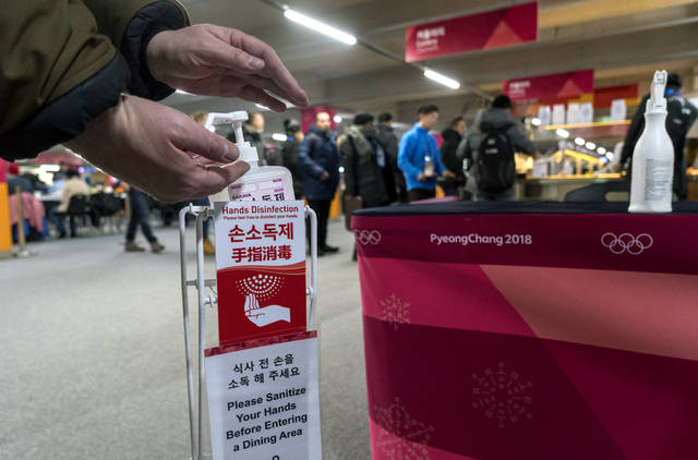 In this Wednesday, Feb. 7, 2018 photo, a man sanitizes his hands at the entrance to the media cafeteria, in Gangneung, South Korea. Another 19 cases of norovirus have been reported at the Pyeongchang Olympics. That brings the total confirmed cases to 177 since Feb. 1. (Paul Chiasson/The Canadian Press via AP)