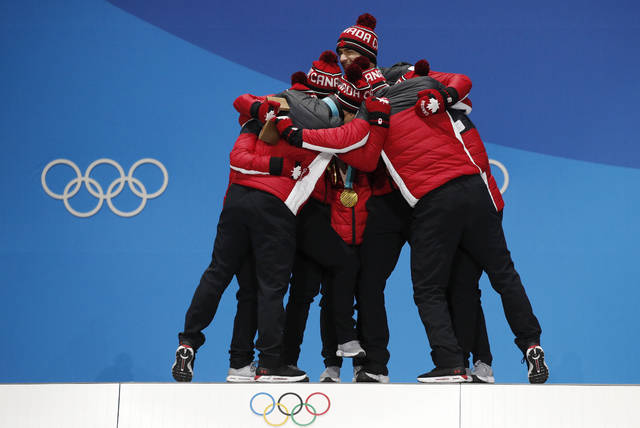 Team figure skating gold medalists from Canada embrace during their medals ceremony at the 2018 Winter Olympics in Pyeongchang, South Korea, Monday, Feb. 12, 2018. (AP Photo/Jae C. Hong)