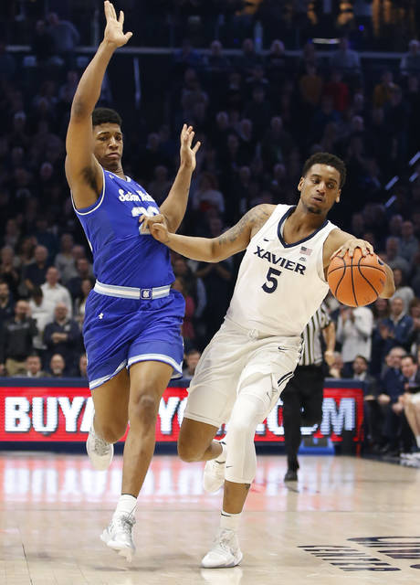 Xavier guard Trevon Bluiett (5) moves the ball against Seton Hall forward Desi Rodriguez (20) during the first half of an NCAA college basketball game Wednesday Feb. 14, 2018, in Cincinnati. (AP Photo/Gary Landers)