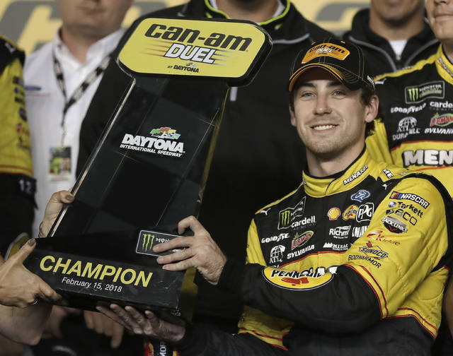 Ryan Blaney raises the trophy in Victory Lane after winning the first of two qualifying races for the NASCAR Daytona 500 auto race at Daytona International Speedway in Daytona Beach, Fla., Thursday, Feb. 15, 2018. (AP Photo/Chuck Burton)