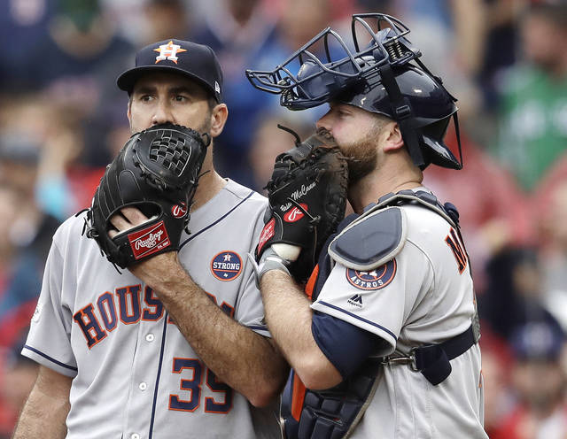 FILE - In this Oct. 9, 2017, file photo, Houston Astros relief pitcher Justin Verlander, left, and catcher Brian McCann talk during the fifth inning of Game 4 of baseball's American League Division Series against the Boston Red Sox in Boston. Major League Baseball is imposing stricter limits on mound visits in an effort to speed games but decided against 20-second pitch clocks for 2018. The new rules announced Monday, Feb. 19, 2018, include a general limit of six mound visits per nine-inning game without a pitching change, whether by a manager, coach or player.  (AP Photo/Charles Krupa, File)